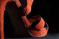Λεπτομέρεια στα κόκκινα θηλυκά υψηλά παπούτσια τακουνιών σε ένα μαύρο υπόβαθρο Στοκ Φωτογραφία