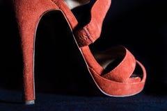 Λεπτομέρεια στα κόκκινα θηλυκά υψηλά παπούτσια τακουνιών σε ένα μαύρο υπόβαθρο Στοκ Φωτογραφίες