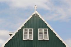 Λεπτομέρεια στεγών ενός ξύλινου σπιτιού της Ολλανδίας στο πράσινο χρώμα με δύο άσπρα παράθυρα σε έναν μπλε ουρανό στοκ φωτογραφίες