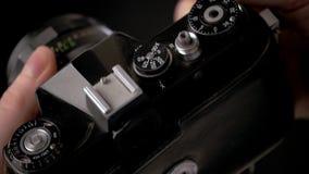 Λεπτομέρεια της εκλεκτής ποιότητας παλαιάς κάμερας για τη δημιουργικότητα φωτογραφίας με στενό επάνω χεριών απόθεμα βίντεο
