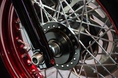 Λεπτομέρεια της μαύρης ρόδας μιας προσαρμοσμένης μοτοσικλέτας που επιχρωμιώνεται με τις κόκκινες και ασημένιες ρόδες στοκ φωτογραφία