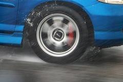 Λεπτομέρεια της οπίσθιας ρόδας μιας οδήγησης αυτοκινήτων στη βροχή στοκ φωτογραφία με δικαίωμα ελεύθερης χρήσης