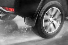 Λεπτομέρεια της οπίσθιας ρόδας μιας οδήγησης αυτοκινήτων στη βροχή Στοκ Εικόνες