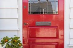 Λεπτομέρεια της λουστραρισμένης με λάκκα κόκκινης μπροστινής πόρτας σε ένα σπίτι Στοκ φωτογραφία με δικαίωμα ελεύθερης χρήσης