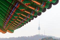 Λεπτομέρεια της παραδοσιακής κορεατικής στέγης με τον πύργο Ν Σεούλ στο υπόβαθρο στοκ εικόνα