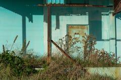 Λεπτομέρεια της πόρτας που εισβάλλεται με τα ζιζάνια στο εγκαταλειμμένο εργοστάσιο κοντά στο ΝΕ Στοκ Φωτογραφία