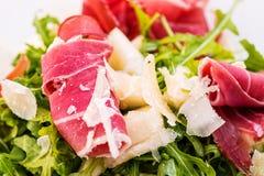 Λεπτομέρεια της φρέσκιας φυτικής σαλάτας arugula με το ζαμπόν και του τυριού στο πιάτο γυαλιού στο άσπρο υπόβαθρο, φωτογραφία προ Στοκ Εικόνα