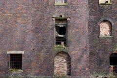 Λεπτομέρεια του εγκαταλελειμμένου κτηρίου τούβλου, επιβιβασμένα παράθυρα στοκ εικόνες