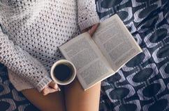 Λεπτομέρεια του προκλητικού νέου φωτός γυναικών και ήλιων Η γυναίκα κρατά ένα φλυτζάνι καφέ και διάβασε ένα βιβλίο Στοκ Εικόνες