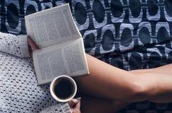 Λεπτομέρεια του προκλητικού νέου φωτός γυναικών και ήλιων Η γυναίκα κρατά ένα φλυτζάνι καφέ και διάβασε ένα βιβλίο Στοκ Εικόνα