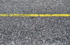 Λεπτομέρεια του δρόμου ασφάλτου με την κίτρινη γραμμή Στοκ εικόνες με δικαίωμα ελεύθερης χρήσης
