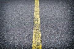 Λεπτομέρεια του δρόμου ασφάλτου με την κίτρινη γραμμή Στοκ Εικόνες