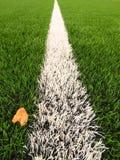 Λεπτομέρεια του τεχνητού τομέα χλόης στην παιδική χαρά ποδοσφαίρου Λεπτομέρεια μιας γραμμής σε ένα γήπεδο ποδοσφαίρου, κίτρινο φύ Στοκ Φωτογραφίες