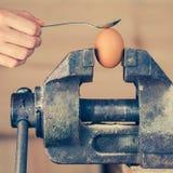 Λεπτομέρεια του χεριού με το κουτάλι που τρυπά ένα αυγό που καθορίζεται στην κακία (χρώμα Στοκ Εικόνες