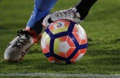 Λεπτομέρεια των ποδιών ενός ποδοσφαιριστή που τρέχει με τη σφαίρα Στοκ εικόνα με δικαίωμα ελεύθερης χρήσης