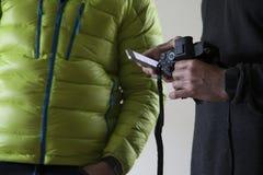 Λεπτομέρεια των χεριών ενός λευκού που κρατά ένα από τα χέρια του με μια κάμερα και με άλλο το κινητό τηλέφωνό του στοκ εικόνα με δικαίωμα ελεύθερης χρήσης
