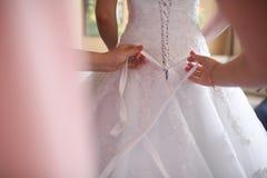 Λεπτομέρεια των χεριών που ρυθμίζουν τη δαντέλλα γαμήλιων φορεμάτων στοκ φωτογραφία