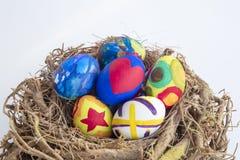 Λεπτομέρεια των χρωματισμένων αυγών Πάσχας που τοποθετούνται σε μια φωλιά με τα διαφορετικά FO Στοκ Εικόνες