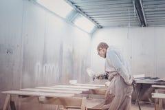 Λεπτομέρειες επίπλων ζωγραφικής ατόμων Εργαζόμενος που χρησιμοποιεί το πυροβόλο όπλο ψεκασμού Στοκ Εικόνες
