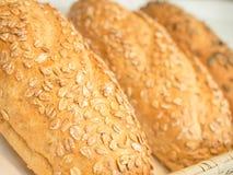 Λεπτομέρειες κινηματογραφήσεων σε πρώτο πλάνο της φρέσκιας ψημένης βρώμης ζωτικής σημασίας ψωμί με τις νιφάδες βρωμών Στοκ Εικόνες