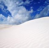 Λεπτομέρειες της άσπρης άμμου και των δραματικών σύννεφων Στοκ Φωτογραφία