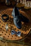 Λεπτομέρειες του γαμήλιου πρωινού των παπουτσιών της νύφης, λουρί, πεταλούδα, ρολόγια στοκ φωτογραφίες