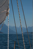 Λεπτομέρειες sailboat, άσπρου ενός πανιού, των σανίδων σωτηρίας και των φύλλων πριν από το μουτζουρωμένο υπόβαθρο της θάλασσας κα Στοκ εικόνα με δικαίωμα ελεύθερης χρήσης