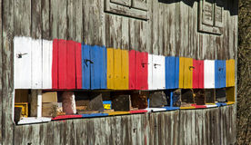 Λεπτομερής άποψη ενός παλαιού ξύλινου ζωηρόχρωμου μελισσουργείου και πετώντας μελισσών που φέρνουν το μέλι Στοκ εικόνες με δικαίωμα ελεύθερης χρήσης