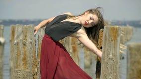 Λεπτός ένας ξανθός με μακρυμάλλη σε ένα κόκκινο φόρεμα κρατά επάνω στις ξύλινες θέσεις κάτω από τα μπουρίνια του αέρα, στη μέση απόθεμα βίντεο