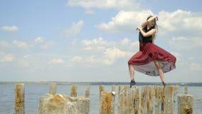 Λεπτός ένας ξανθός με μακρυμάλλη σε ένα κόκκινο φόρεμα στέκεται στις ξύλινες θέσεις κάτω από τα μπουρίνια του αέρα, στη μέση φιλμ μικρού μήκους