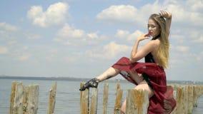 Λεπτός ένας ξανθός με μακρυμάλλη σε μια κόκκινη τοποθέτηση φορεμάτων που κλίνει στις ξύλινες θέσεις κάτω από τα μπουρίνια του αέρ φιλμ μικρού μήκους