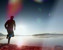 Λεπτός νέος δρομέας ατόμων ικανότητας στην παραλία, τροπικός δρομέας ιχνών Αθλητικός τύπος που οργανώνεται εύθυμος στην παραλία Στοκ Εικόνες