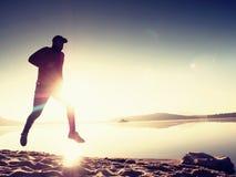 Λεπτός νέος δρομέας ατόμων ικανότητας στην παραλία, τροπικός δρομέας ιχνών Αθλητικός τύπος που οργανώνεται εύθυμος στην παραλία Στοκ Φωτογραφίες
