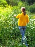 Λεπτός ταξιδιώτης γυναικών στο κίτρινο σακάκι για έναν περίπατο μεταξύ της πράσινης χλόης στοκ φωτογραφίες