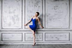 Λεπτός όμορφος ξανθός είναι για τον εκλεκτής ποιότητας τοίχο Κορίτσι στο μπλε φόρεμα και μοντέρνα παπούτσια με τα μακριά πόδια Στοκ Φωτογραφίες