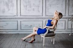 Λεπτός όμορφος ξανθός είναι για τον εκλεκτής ποιότητας τοίχο Κορίτσι στο μπλε φόρεμα και μοντέρνα παπούτσια με τα μακριά πόδια Στοκ εικόνα με δικαίωμα ελεύθερης χρήσης