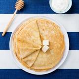 Λεπτός crepes ή τηγανίτες με το βούτυρο, το μέλι και το ξινό διάστημα αντιγράφων άποψης κρέμας τοπ Στοκ Φωτογραφία