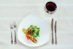 Λεπτό έξοχο μίγμα Migdal Τουρκία σαλάτας σε ένα άσπρο πιάτο με το κρασί και τον πίνακα που θέτει σε ένα άσπρο τραπεζομάντιλο Στοκ Εικόνα