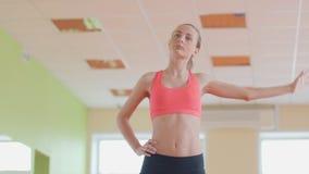 Λεπτό αθλητικό κορίτσι που κάνει τις ασκήσεις γιόγκας εσωτερικές τέντωμα φιλμ μικρού μήκους