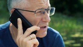 Λεπτό γκρίζος-μαλλιαρό σοβαρό άτομο σε μια μπλε μπλούζα και τα γυαλιά που μιλούν αυστηρά στο τηλέφωνο, που κάθεται σε μια βάρκα απόθεμα βίντεο