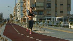 Λεπτό γυναικείο κατά μήκος του αστικού δρόμου Ενεργός τρόπος ζωής για το wellness και την υγεία απόθεμα βίντεο