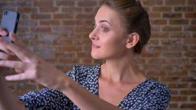 Λεπτό καυκάσιο θηλυκό brunette, που παίρνει selfie και που χαμογελά στεμένος στην ψύχρα στούντιο τούβλου φιλμ μικρού μήκους