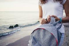 Λεπτό κορίτσι που κρατά ένα σακίδιο πλάτης στην παραλία Στοκ Εικόνες