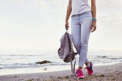 Λεπτό κορίτσι στα τζιν και τα πάνινα παπούτσια, που περπατούν κατά μήκος της παραλίας Στοκ Εικόνες