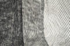 Λεπτό μαύρο πρόστιμο - πλέγμα με τα τσαλακωμένα κύματα στο άσπρο υπόβαθρο und Στοκ Εικόνες