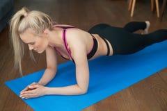 Λεπτό ξανθό κορίτσι αθλητών γυναικών ικανότητας νέο που κάνει την άσκηση σανίδων στο σπίτι στο χαλί στοκ εικόνα με δικαίωμα ελεύθερης χρήσης
