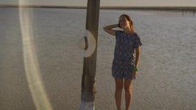 Λεπτό προκλητικό κορίτσι που απολαμβάνει το ηλιοβασίλεμα, στάσεις κοντά σε έναν ξύλινο αλατισμένο στυλοβάτη μιας αλατισμένης λίμν απόθεμα βίντεο