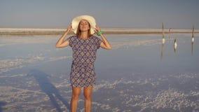 Λεπτό προκλητικό κορίτσι στο άσπρο καπέλο που απολαμβάνει το ηλιοβασίλεμα, ξύλινοι αλατισμένοι στυλοβάτες μιας αλατισμένης λίμνης απόθεμα βίντεο