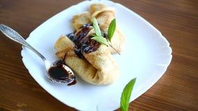 Λεπτύντε τις τηγανισμένες τηγανίτες που γεμίζονται με τη μαρμελάδα σε ένα πιάτο απόθεμα βίντεο