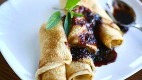 Λεπτύντε τις τηγανισμένες τηγανίτες που γεμίζονται με τη μαρμελάδα σε ένα πιάτο φιλμ μικρού μήκους